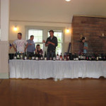 Wine Tasting event - long table with white tablecloth, wines lined up on table, and wine reps behind table.