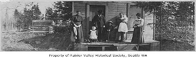 Old fashioned photo of the first family to move into Lakewood standing on the porch of their simple wood house.