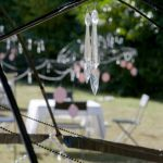 Outdoor view, decorated for anniversary with hanging crystals; white table and chairs outside
