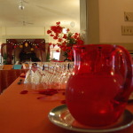 Red glass pitcher on silver platter on table. Empty wine glasses set upside down next to pitcher. Red decorations in background.