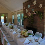 Long table by fireplace decorated with white table cloth, napkins, yellow flowers; wedding decorations